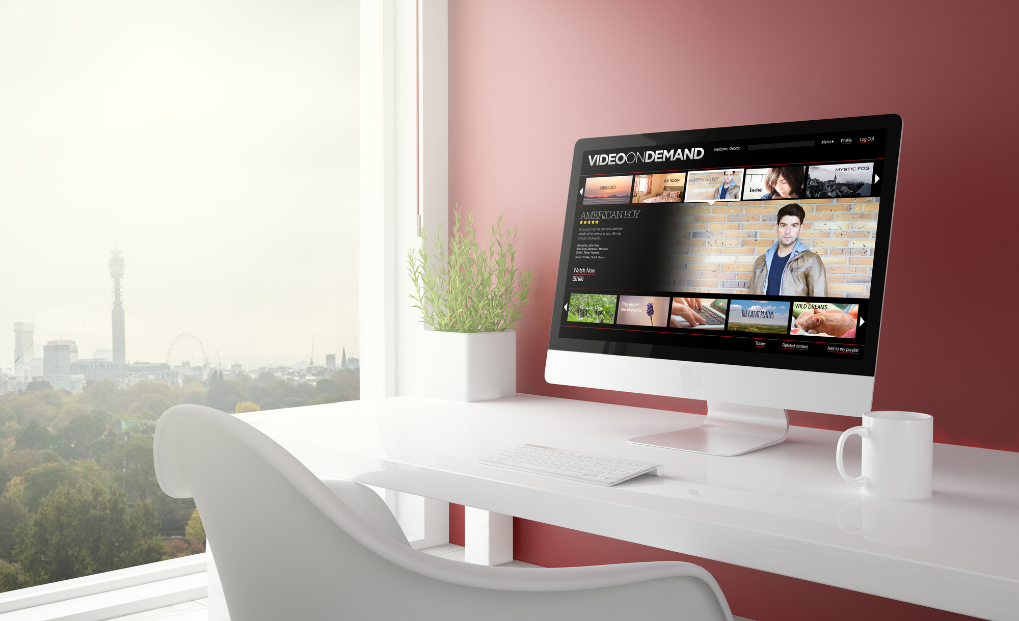 """A computer monitor on a white desk with a web browser open to a """"video on demand"""" page. At the left side of the photo, a tree and a cityscape are visible outside of a window."""
