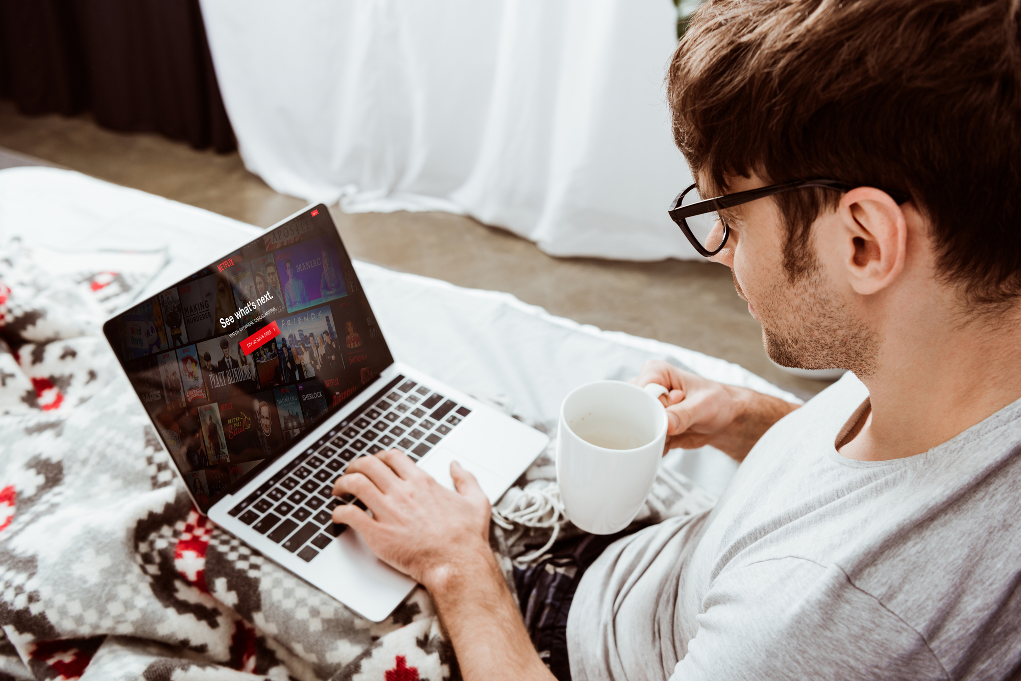 A person watches Netflix on their laptop in bed. In their right hand, they are holding a white mug.