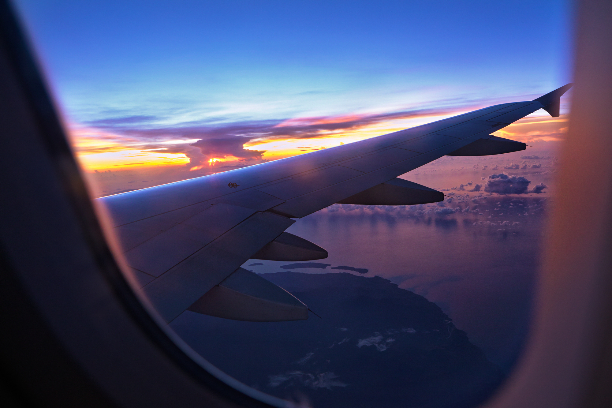 A sunset over the wing of a plane viewed from the plane's window. Below, a coastline and sporadic clouds are visible.