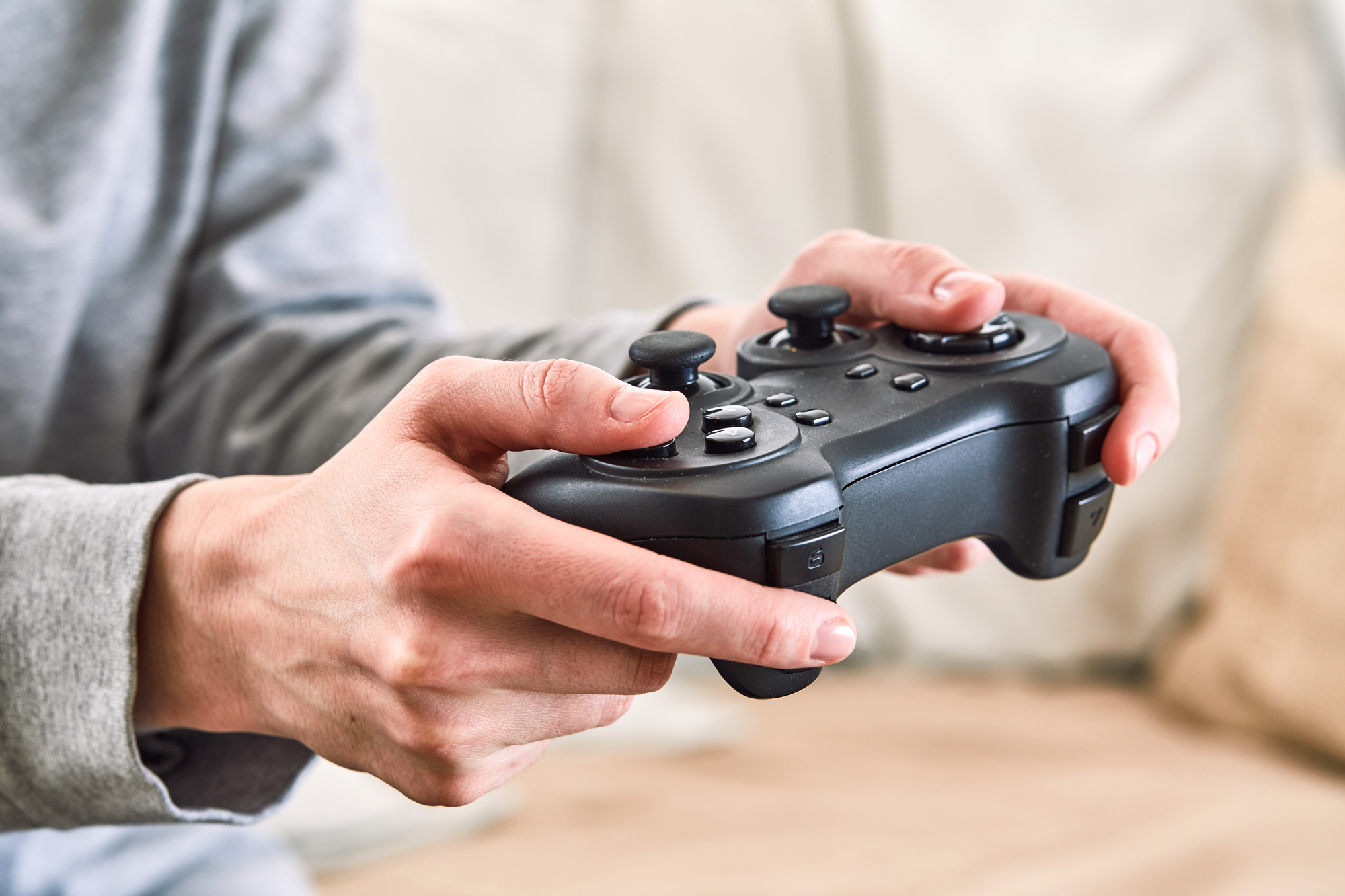 A person's hands are holding a video game controller. The rest of the person isn't visible and the room behind them is blurred.